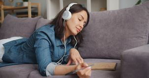 Creative girl listening to music through headphones and drawing picture at home. Creative girl is listening to music through headphones and drawing picture at stock video footage