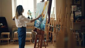 Creative girl is painting beautiful picture standing in light workshop holding palette and brush using tools to create stock footage