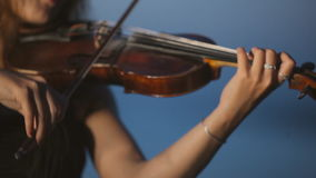 Creative girl playing the violin standing on a stock footage