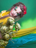 Creative girl. Spring fairy. Young woman in creative image posing with bright fabric's and flowers Stock Photo