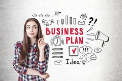 Creative girl with a thumb up, business plan. Portrait of a creative young woman wearing a checkered shirt and looking sideways while thinking and pointing Royalty Free Stock Photography