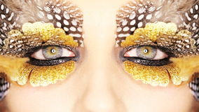 Creative golden eye makeup. Creative golden eyes make-up with bird lashes stock footage