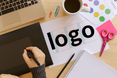 Creative graphic designer using a graphics tablet at work. Logo design concept. Flat lay Royalty Free Stock Photography