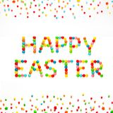 Creative Greeting card Happy Easter. Text Happy Easter made of multicolored sweet candy dragees and decorated colored sprinkles on isolated white background Stock Photography
