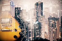 Creative guitar on city background. Creative image of electric guitar on night city background. Art and music concept. Double exposure Stock Images