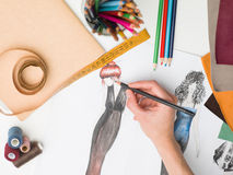 Creative hand. Female hand drawing fashion sketch on desk with designing equipment Stock Photo