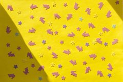 Creative Happy Easter - pink rabbits, bunnies, flowers on yellow paper colorful modern geometric background in sunlight. Flat lay royalty free stock image