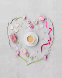Creative heart in flatlay style made from flowers, gift, cup of coffee and decorations on table from above for Valentines day. Stock Photo