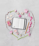 Creative heart in flatlay style made from flowers, gift, empty notebook and decorations on table from above for Valentines day. Royalty Free Stock Images