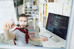 Creative hipster coder working with programming language. Serious confident young creative hipster coder in casual clothing sitting at table with powerful stock images