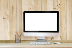Creative hipster desktop with blank white computer screen, coffee cup and other items on white brick background. Stock Photo