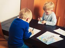 Kids playing together, drawing pictures on paper Stock Images