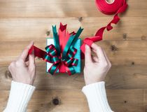 Creative hobby. Woman `s hands wrap christmas holiday handmade. Present in craft paper with twine ribbon. Making bow gift box, decorated with cute object on royalty free stock images