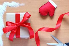 Creative hobby. Wrap christmas holiday handmade present in craft paper with red ribbon. Making bow at xmas gift box. stock photos