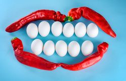 Beautiful smile from white eggs and red pepper. White teeth, happy lifestyle. Free space and background to text. A creative idea for advertising a dental clinic stock image