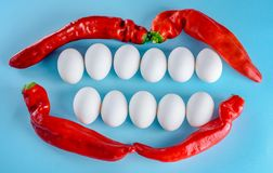 Beautiful smile from white eggs and red pepper. White teeth, happy lifestyle. A creative idea for advertising a dental clinic and dentistry.Beautiful smile from stock images