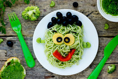 Creative idea for baby dinner or lunch - green spaghetti monster. With broccoli, parsley, celery, black olives and pepper. Concept of funny and healthy meal Royalty Free Stock Photos