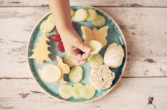 Creative idea for child food. Funny breakfast. Children's hand holds cucumber. Sandwiches in the shape of a bunny, butterfly Stock Image