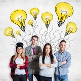 Creative idea concept. Attractive young team on concrete background with drawn light bulbs. Creative idea concept Stock Image