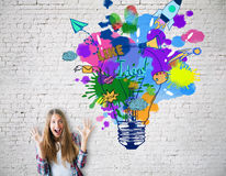 Creative idea concept. Excited caucasian girl on brick background with colorful lamp sketch. Creative idea concept Stock Photos