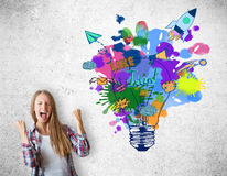Creative idea concept. Happy caucasian girl with colorful light bulb sketch on concrete background. Creative idea concept Royalty Free Stock Images