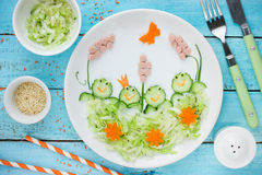 Creative idea for healthy food for kids - cucumber cabbage salad. Shaped funny frogs on a swamp Stock Image