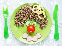 Creative idea for kids dinner or breakfast - buckwheat with sausage and vegetables in the shape of clown face. Fun food art for c stock photo