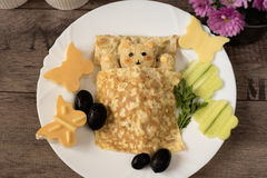 Creative idea for kids snack, breakfast or lunch. Sleeping bear from bulgur, rice and quinoa under the blanket of egg omelet. Flowers and butterflies with stock image