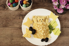 Creative idea for kids snack, breakfast or lunch. Sleeping bear from bulgur, rice and quinoa under the blanket of egg omelet. Flowers and butterflies with stock photos