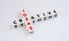 Creative ideas. Text ' creative ' and ' ideas ' in uppercase letters on white cubes arranged crossword style with common letter ' e ', white background Royalty Free Stock Photo