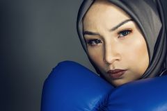 Creative ideas concept, aggrassive young muslimah businesswomen with boxing glove over dark background Stock Photos