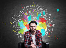 Creative ideas concept. Handsome european guy sitting on chalkboard background with colorful business sketch. Creative ideas concept Royalty Free Stock Photo