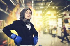 Successful and aggressive young muslimah businesswomen with boxing glove over abstract double exposure background. Creative ideas concept, successful and Stock Photos