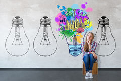Creative ideas concept. Thoughtful young girl sitting in interior with drawn light bulbs and business sketch. Creative ideas concept Stock Photo