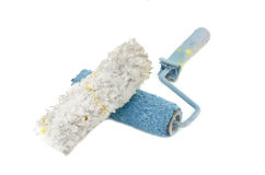 Creative image of dirty and reused white and blue roller paint brush with white feather placed in front Royalty Free Stock Photo