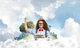 Creative inspiration of young female writer. Young and beautiful woman writer in hat and eyeglasses using typing machine and pointing upside while sitting at Stock Photo