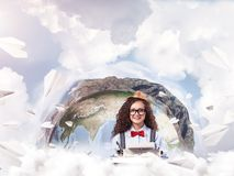Creative inspiration of young female writer. Hard-working female writer using typing machine while sitting at the table with flying paper planes and Earth globe stock photography