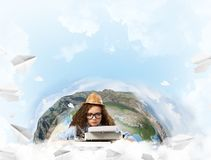 Creative inspiration of young female writer. Hard-working female writer using typing machine while sitting at the table with flying paper planes and Earth globe stock images