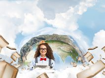 Creative inspiration of young female writer. Portrait of hard-working female writer using typing machine while sitting at the table with flying papers and Earth stock images