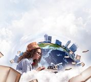 Creative inspiration of young female writer. Portrait of hard-working female writer using typing machine while sitting at the table with flying papers and Earth royalty free stock photography