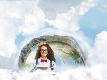 Creative inspiration of young female writer. Young woman writer in hat and eyeglasses using typing machine while sitting at the table with Earth globe and Royalty Free Stock Photography