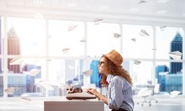 Creative inspiration of young female writer. Young woman writer in hat and eyeglasses using typing machine while sitting at the table indoors among flying paper Royalty Free Stock Image
