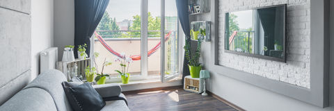 Creative interior design. Panoramic view of creative interior design with sofa, big tv, homemade decorations and balcony Royalty Free Stock Image