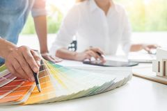 Creative or Interior designers teamwork with pantone swatch and. Building plans on office desk, architects choosing color samples for design project stock photo