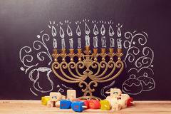 Creative Jewish holiday Hanukkah background with menorah and spinning tops over chalkboard. With hand drawing Stock Images