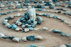 Traditional natural stone labyrinth maze made for contemplation and worship, created with rocks in shades of blue and turquoise stock photography