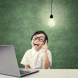 Creative kid with laptop pointing at lamp Royalty Free Stock Images