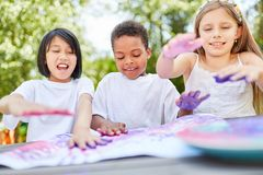 Creative kids play with finger paints. Creative kids as friends play with finger paints on kids birthday Royalty Free Stock Photos
