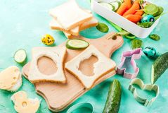 Creative kids breakfast lunch box for Easter. Cooking creative kids breakfast lunch box for Easter, sandwiches with cheese, fresh vegetables - cucumbers, carrots stock photos