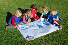 Creative kids team. A group of five Caucasian children sitting outdoors in the garden and concentrating on painting one big picture together for the school's
